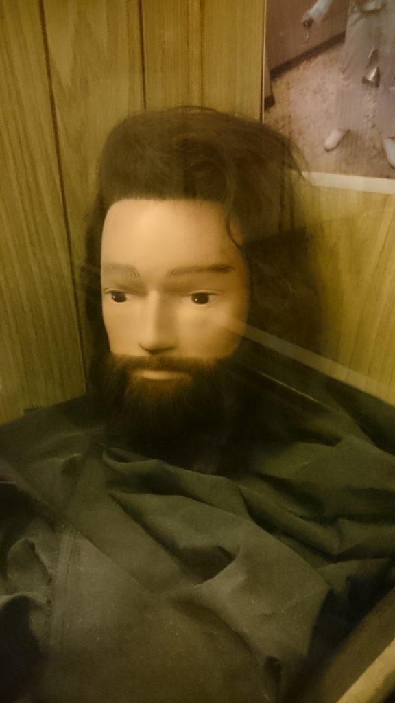 Dukkehode med skjegg i vinduet til en frisørsalong.
