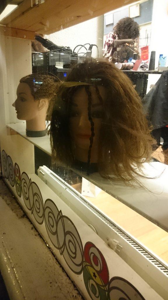 Dukkehoder i vinduet til en frisør viser hva de kan, eller?